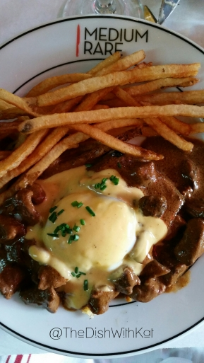 Steak Benedict is an entree option that includes sliced steak and portabella mushrooms and is served with frites and a delicious hollandaise sauce.