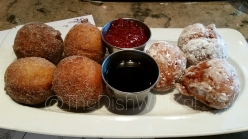 The powered sugar and cinnamon sugar Rustico Doughnuts are served with seasonal preserves and chocolate sauce.