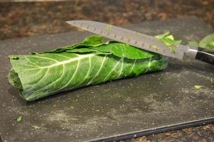 Roll a bunch of collard leaves tightly.